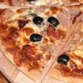 Kawałek pysznej pizzy z tuńczykiem, czarnymi oliwkami, suszonymi pomidorami i kaparami